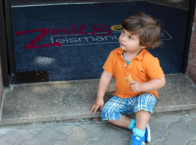 Kind mit Eiswaffel auf der Türschwelle
